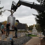 Manipulation délicate du moulin vers son socle de granit au centre du pavillon