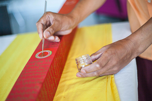 Lama Jampa et Sylvestre à l'œuvre pour apposer la poudre d'or